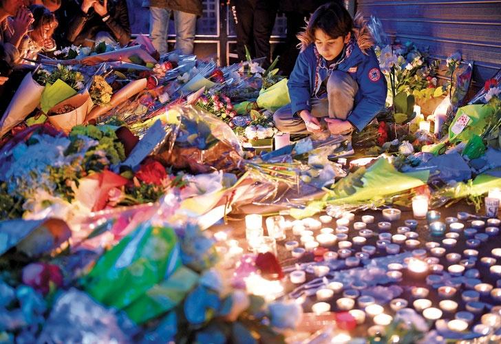 Sin consuelo. Un niño francés participa de los homenajes a las víctimas frente a uno de los locales donde los yihadistas asesinaron a decenas de personas. Las fuerzas de seguridad galas se movilizaron ayer en la capital ante el pánico civil por los atentados.