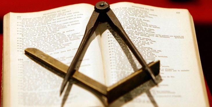 El Libro de la Ley Sagrada sostiene la Escuadra y el Compás que se apoyan sobre ella.